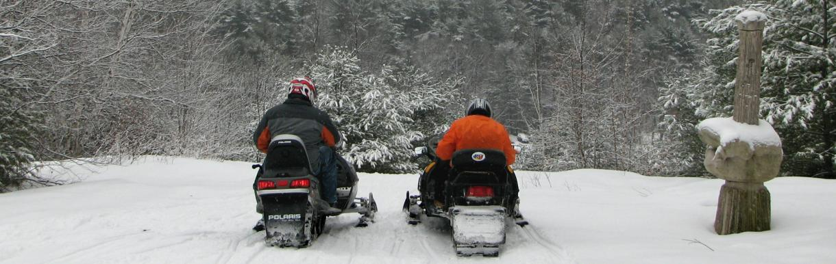 Rear view of 2 snowmobilers in full winter gear at andres overlooking town library