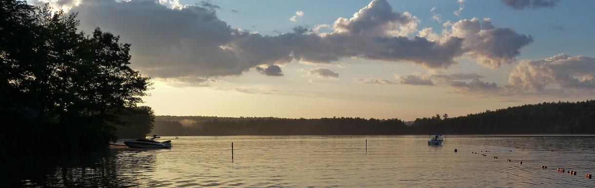 Clouds at dusk over calm water - few boats in water, trees along short at left