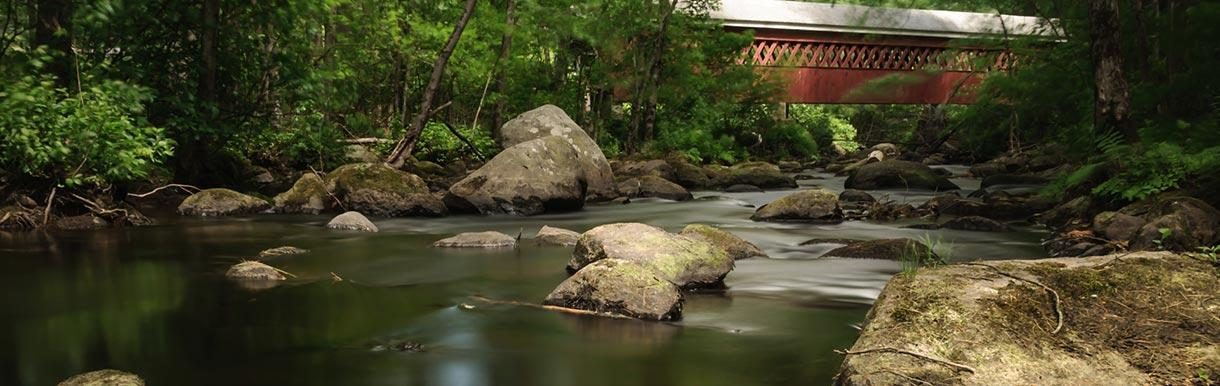Covered bridge spanning calm stream